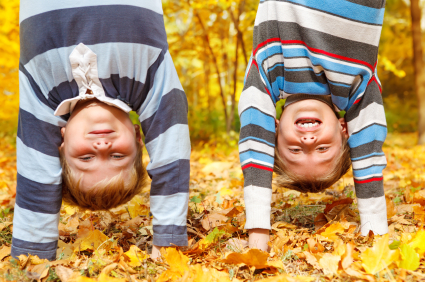 Two kids Standing on their hands in a pile of leaves
